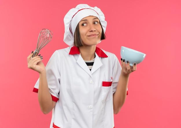 Lieta giovane donna cuoca in uniforme da chef tenendo la frusta e la ciotola e guardando il lato isolato sulla parete rosa