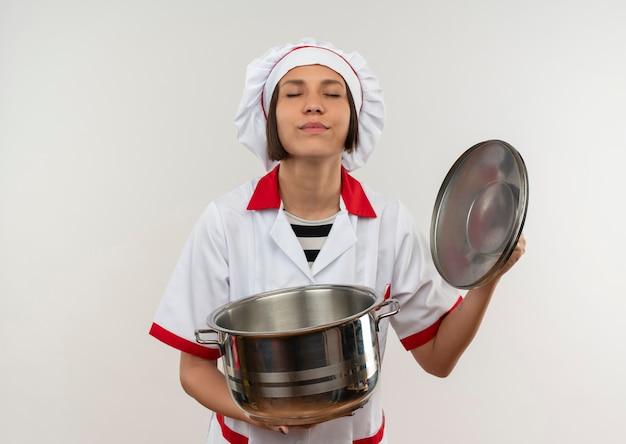 Lieta giovane cuoca in uniforme da chef aprendo il coperchio della pentola con gli occhi chiusi isolato sul muro bianco