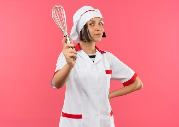 Lieta giovane cuoca in uniforme da chef mettendo la mano sulla vita e allungando la frusta verso la parte anteriore isolata sul muro rosa