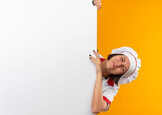 Lieta giovane cuoca in uniforme da chef in piedi dietro il muro bianco che tiene e che mette la mano su di esso con gli occhi chiusi isolati sulla parete arancione