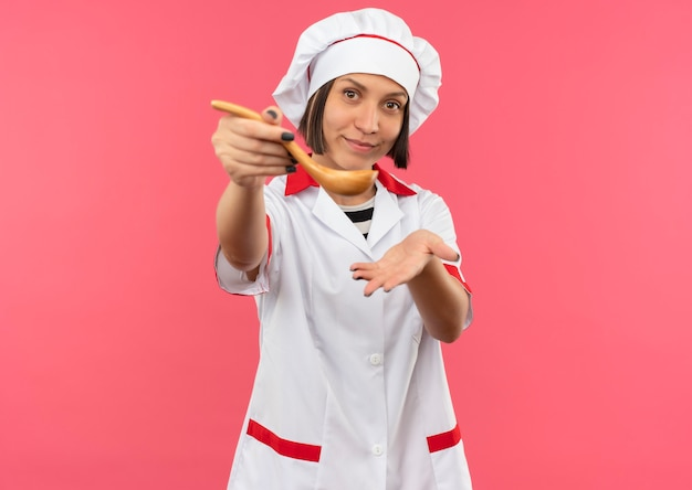 Lieta giovane cuoca in uniforme da chef che allunga il cucchiaio verso la parte anteriore e mostra la mano vuota isolata sul muro rosa