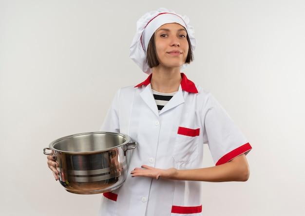 白い背景で隔離の鍋を保持し、指しているシェフの制服を着た若い女性料理人を喜ばせる