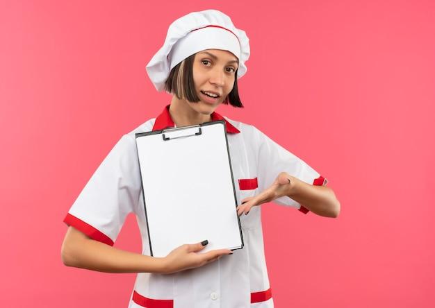 ピンクの背景に分離されたクリップボードを手で持って指さし、シェフの制服を着た若い女性料理人を喜ばせる