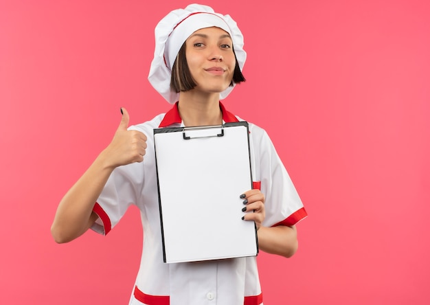 クリップボードを保持し、コピースペースでピンクの背景に分離された親指を見せてシェフの制服を着た若い女性料理人を喜ばせる