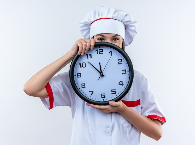 白い壁に分離された壁時計でシェフの制服で覆われた顔を身に着けている若い女性料理人を喜ばせる