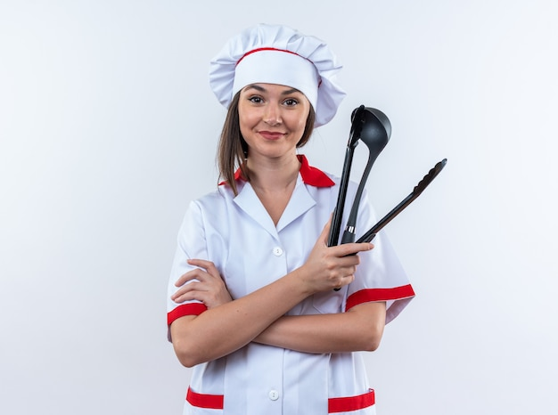 Pleased young female cook wearing chef uniform crossing hands holding spatula with ladle isolated on white wall