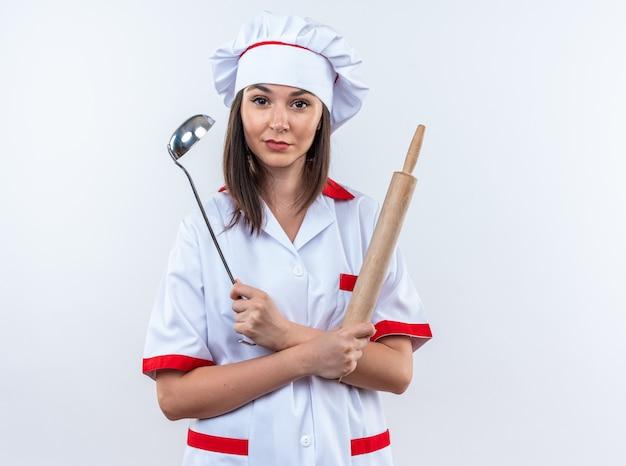 Довольная молодая женщина-повар в униформе шеф-повара держит и пересекает ковш со скалкой, изолированной на белой стене