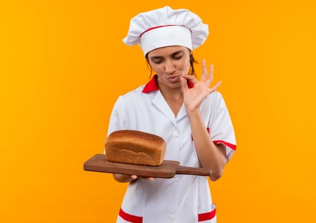 まな板の上でパンを持って見て、コピースペースのある孤立した黄色の壁においしいジェスチャーを示すシェフの制服を着た若い女性料理人を喜ばせます