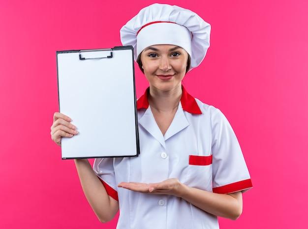 ピンクの背景で隔離のクリップボードに手でシェフの制服を保持し、ポイントを身に着けている若い女性料理人を喜ばせる