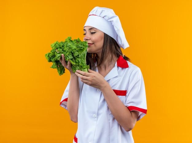 Довольная молодая женщина-повар в униформе шеф-повара держит и нюхает салат на оранжевой стене