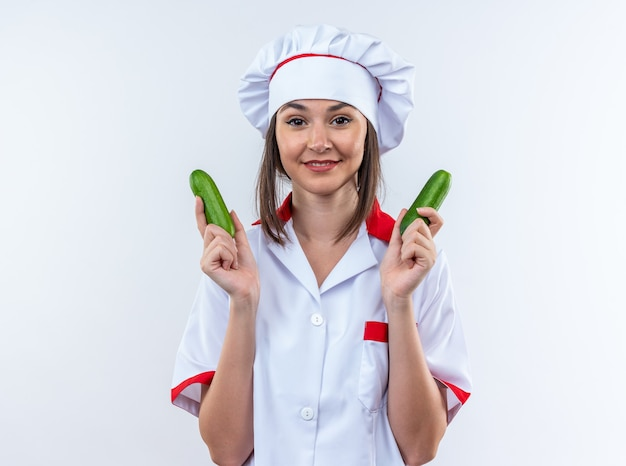 Pleased young female cook wearing chef uniform holding cucumbers isolated on white wall