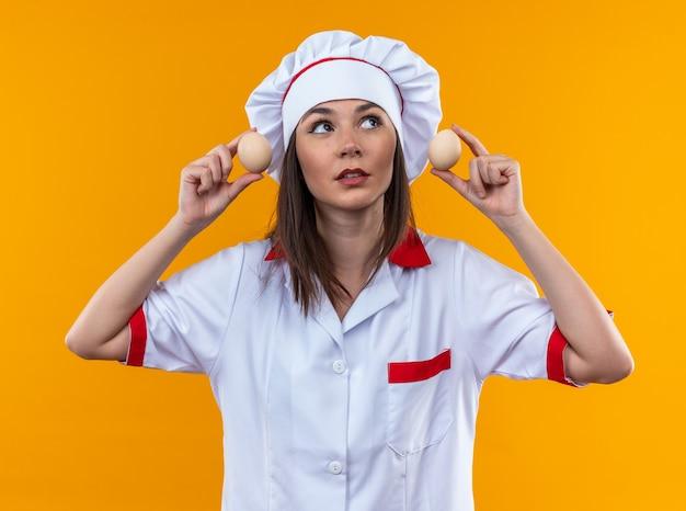 Довольная молодая женщина-повар в униформе шеф-повара держит яйца вокруг ушей, изолированные на оранжевой стене