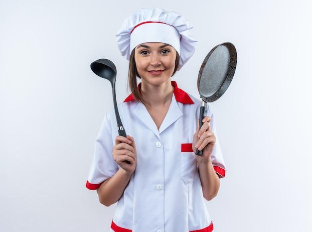 Довольная молодая женщина-повар в униформе шеф-повара держит сковороду с ковшом на белом фоне