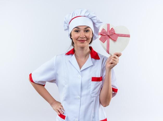 Felice giovane cuoca che indossa l'uniforme dello chef che tiene la scatola a forma di cuore mettendo la mano sull'anca isolata su sfondo bianco white