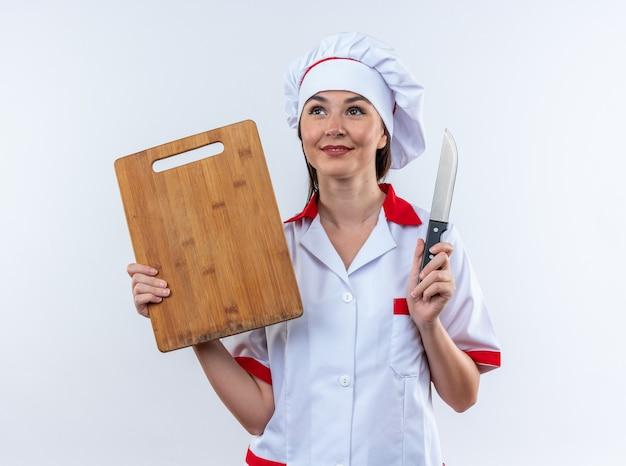 흰 벽에 격리된 도마와 칼을 들고 요리사 유니폼을 입은 젊은 여성 요리사를 기쁘게 생각합니다.