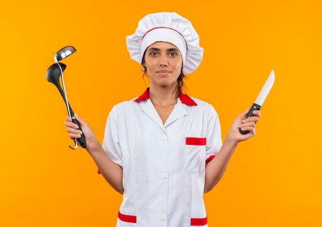 Довольная молодая женщина-повар в униформе шеф-повара держит ковш и нож на изолированной желтой стене с копией пространства