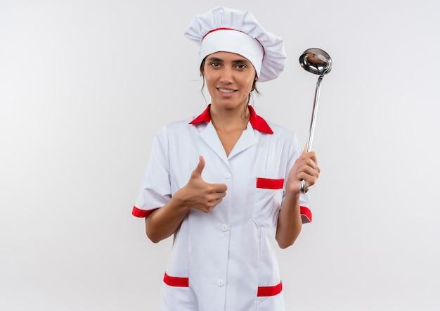 Довольная молодая женщина-повар в униформе шеф-повара держит ковш на изолированной белой стене с копией пространства