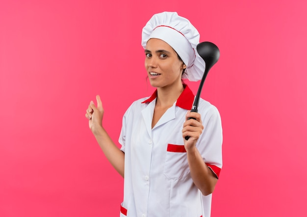 Довольная молодая женщина-повар в униформе шеф-повара держит черпак на розовой стене с копией пространства