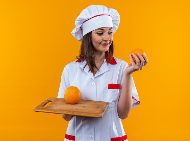 Pleased young female cook wearing chef uniform holding oranges on cutting board isolated on orange wall