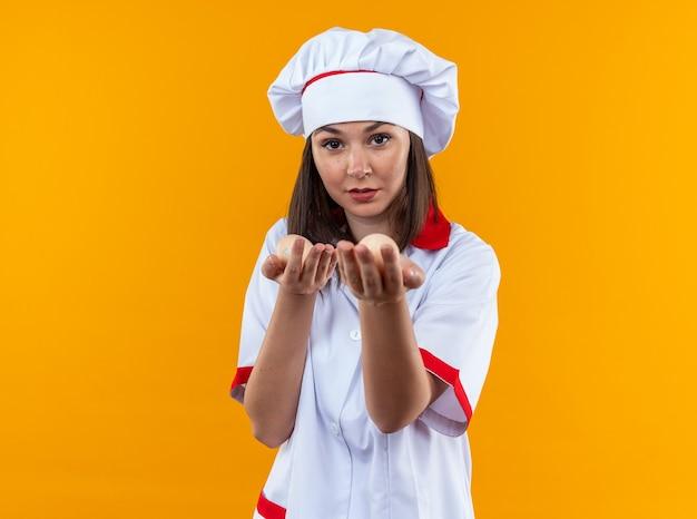 Довольная молодая женщина-повар в униформе шеф-повара протягивает яйца перед камерой, изолированной на оранжевом фоне