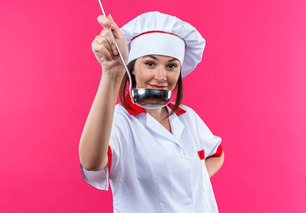 Pleased young female cook wearing chef uniform holding out ladle at front isolated on pink wall
