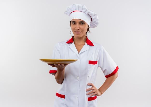 コピースペースのある孤立した白い壁に腰に手を置くシェフの制服保持プレートを身に着けている若い女性料理人を喜ばせる