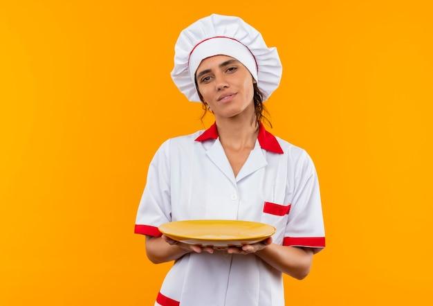 Piacere giovane femmina cuoco indossando chef uniforme tenendo la piastra con copia spazio
