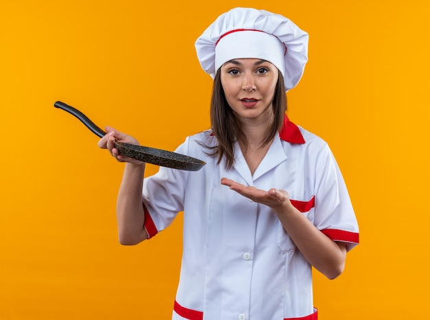 Pleased young female cook wearing chef uniform holding and points with hand at frying pan isolated on orange wall