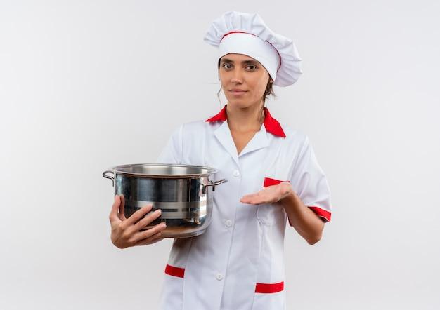 Lieto giovane femmina cuoco indossa chef uniforme holding e punti con pentola a mano sul muro bianco isolato con spazio di copia