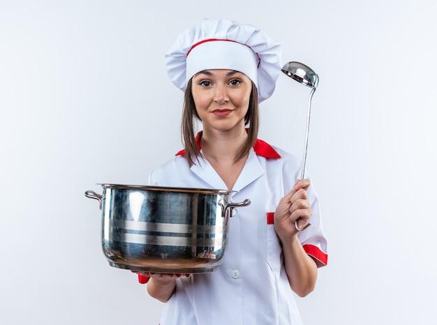 Довольная молодая женщина-повар в униформе шеф-повара держит кастрюлю с ковшом на белом фоне