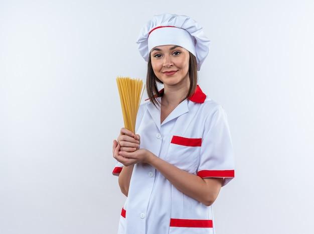 白い背景で隔離のスパゲッティを保持しているシェフの制服を着て喜んで若い女性料理人