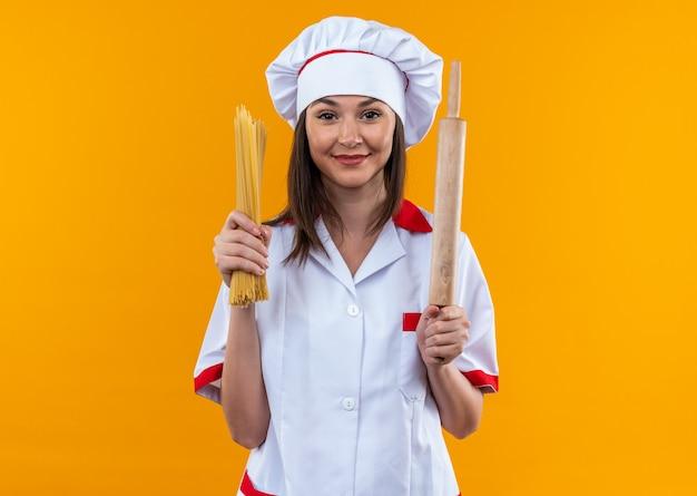 Довольная молодая женщина-повар в униформе шеф-повара держит спагетти со скалкой на оранжевом фоне