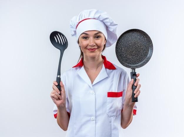 Довольная молодая женщина-повар в униформе шеф-повара держит лопатку со сковородой на белом фоне