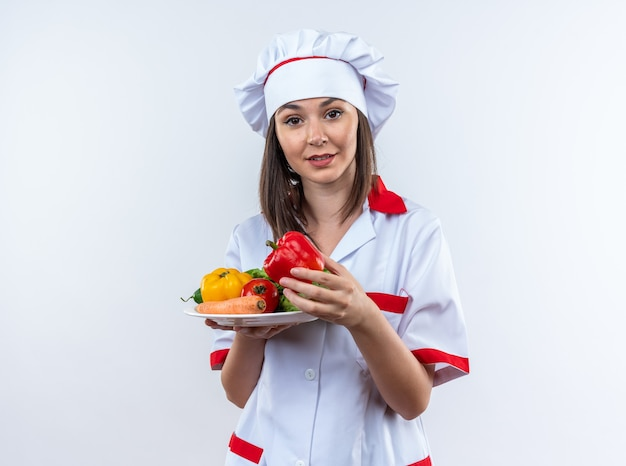 白い壁に隔離されたプレートに野菜を保持しているシェフの制服を着て喜んで若い女性料理人