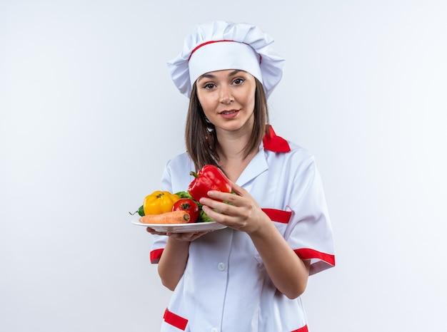 Piacevole giovane cuoca che indossa l'uniforme dello chef tenendo le verdure sulla piastra isolata sul muro bianco
