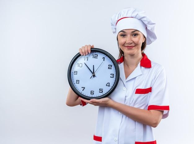 白い背景で隔離の壁時計を保持しているシェフの制服を着て喜んで若い女性料理人