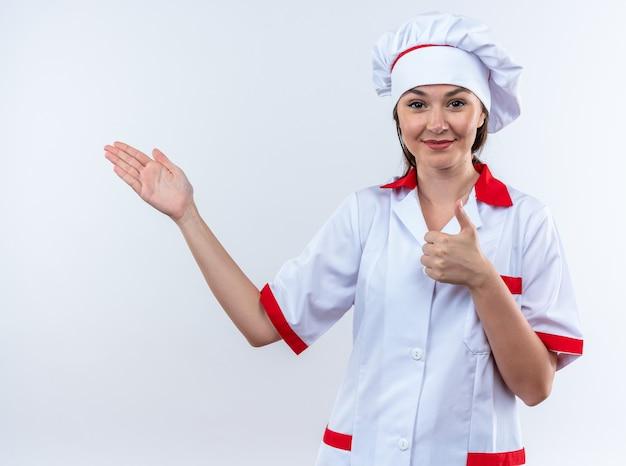 コピースペースで白い壁に隔離された側に親指アップポイントを示すシェフの制服を着て喜んで若い女性料理人