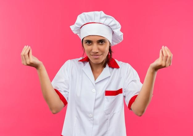 격리 된 분홍색 벽에 팁 제스처를 보여주는 요리사 유니폼을 입고 기쁘게 젊은 여성 요리사