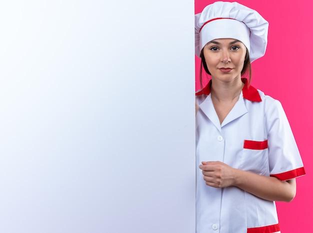 Довольная молодая женщина-повар в униформе шеф-повара стоит рядом с белой стеной, изолированной на розовой стене с копией пространства