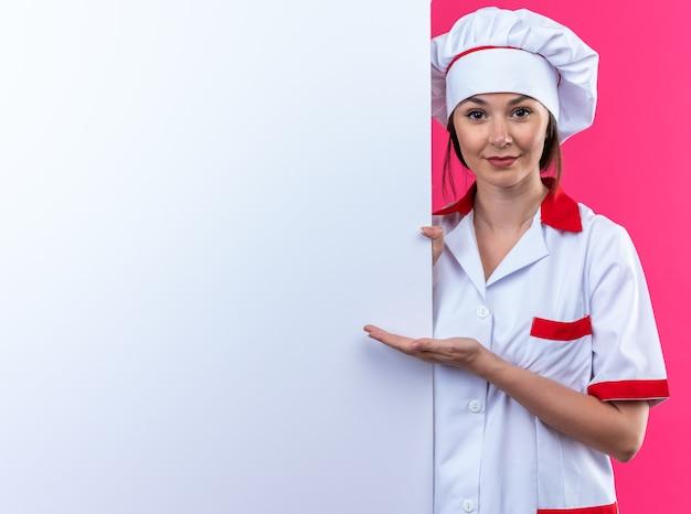Compiaciuta giovane cuoca che indossa l'uniforme dello chef si alza e punta con la mano al vicino muro bianco isolato su parete rosa con spazio copia
