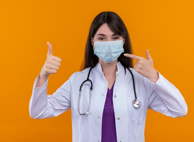 聴診器を備えた医療ローブの満足している若い女性医師は、使い捨ての医療用フェイスマスクの親指を立てて、孤立したオレンジ色の背景のマスクを指しています