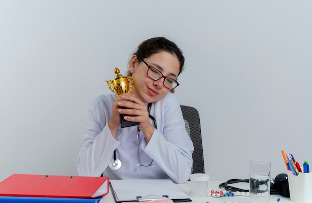 의료 가운 및 청진 기 및 격리 된 닫힌 된 눈으로 우승자 컵을 들고 의료 도구와 책상에 앉아 안경을 착용 기쁘게 젊은 여성 의사
