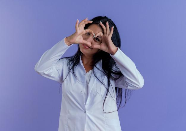 Felice giovane donna medico indossa abito medico cercando facendo segno di cuore