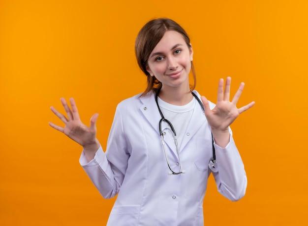 Felice giovane dottoressa indossa veste medica e stetoscopio e mostra le mani vuote sullo spazio arancione isolato