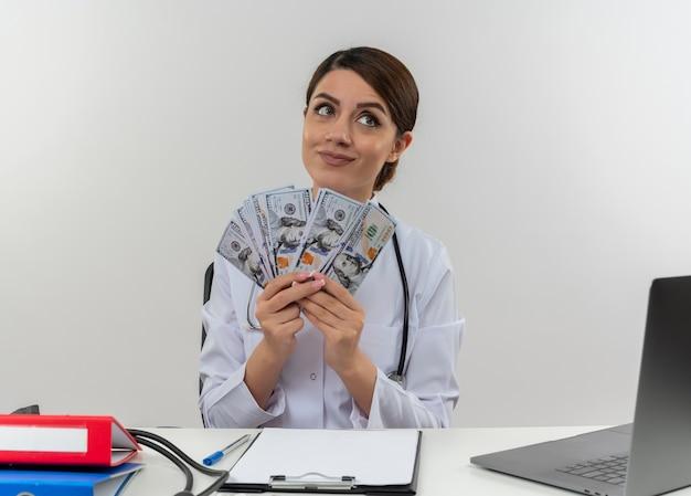 Felice giovane medico femminile che indossa abito medico e stetoscopio seduto alla scrivania con strumenti medici e laptop tenendo i soldi guardando il lato isolato sul muro bianco
