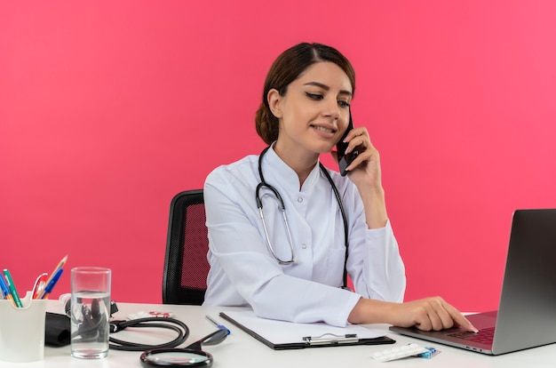 Felice giovane medico femminile che indossa abito medico e stetoscopio seduto alla scrivania con strumenti medici utilizzando laptop parlando al telefono isolato sulla parete rosa