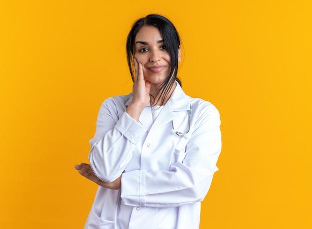 Felice giovane dottoressa che indossa una veste medica con uno stetoscopio che mette la mano sulla guancia isolata sulla parete gialla
