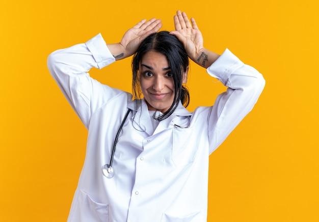 Довольная молодая женщина-врач в медицинском халате со стетоскопом показывает жест кроличьих ушей, изолированный на желтой стене