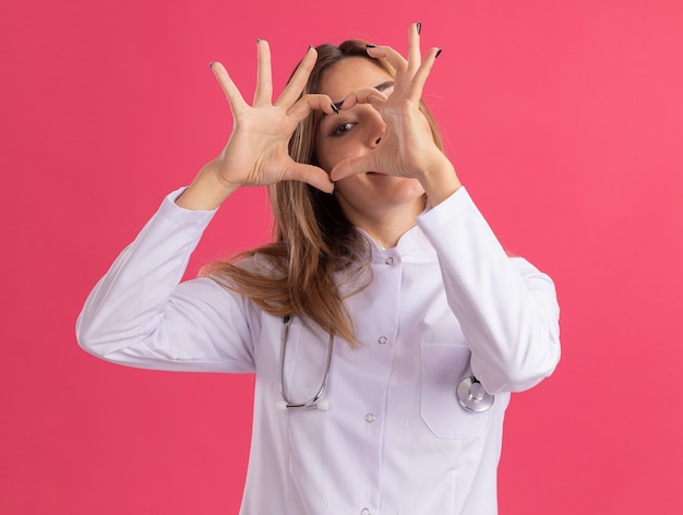 Felice giovane medico femminile che indossa abito medico con lo stetoscopio che mostra il gesto del cuore isolato sulla parete rosa