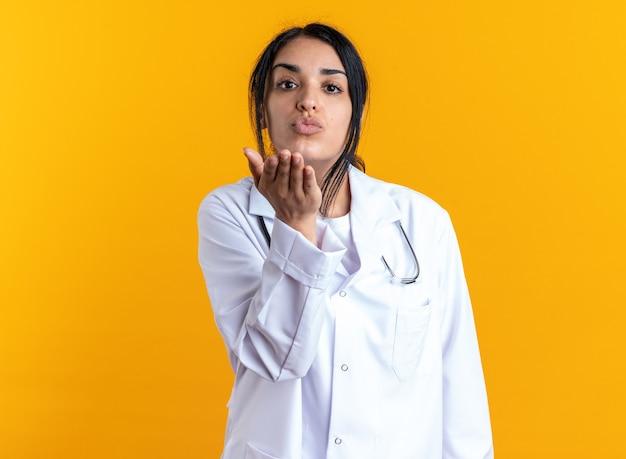 노란색 벽에 고립 된 키스 제스처를 보여주는 청진 기 의료 가운을 입고 기쁘게 젊은 여성 의사
